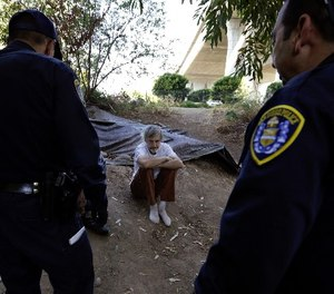 In this Sept. 28, 2017, photo, Stephen Schofield looks on as police officials encourage him to get a Hepatitis A vaccination near where is living along the San Diego River in San Diego.