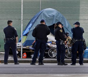 In this March 1, 2016 file photo, San Francisco police officers wait while homeless people collect their belongings in San Francisco. (AP Photo/Ben Margot, File)