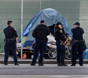 In this March 1, 2016 file photo, San Francisco police officers wait while homeless people collect their belongings in San Francisco.