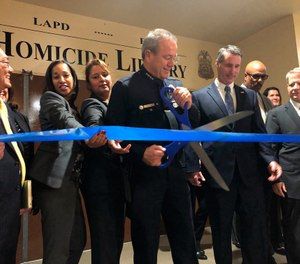Los Angeles Police Chief Michel Moore cuts a ribbon to officially open the city's Homicide Library, where authorities are working to digitize murder cases in Los Angeles Wednesday, Oct. 2, 2019. (AP Photo/Stefanie Dazio)