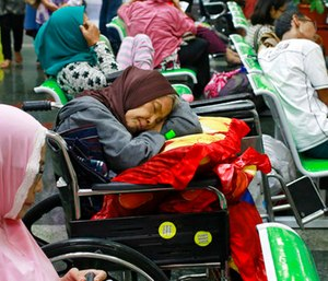 A patient takes a nap on her wheelchair as she waits with others at the registration desk at Dharmais Cancer Hospital in Jakarta, Indonesia.