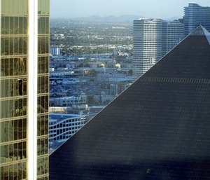 The Mandalay Bay Resort and Casino, at left, with a broken window, stands next to the Luxor in Las Vegas.