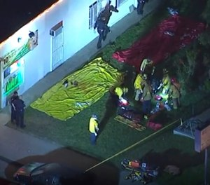 Aerial image made from video shows the scene where emergency workers have cordoned off an area after a shooting inside a home in Long Beach, Calif. (KABC via AP)