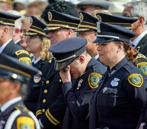 A Houston Police Officer wipes away tears during a funeral service for Houston Police Sgt. Christopher Brewster. (Photo/AP)
