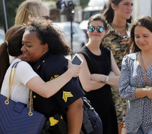 A well-wisher hugs Dallas police Sgt. Jamie Matthews, right, as they both visit a makeshift memorial in front of the departments headquarters, Monday, July 11, 2016, in Dallas. (AP Photo/Tony Gutierrez)