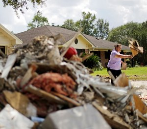 Maria Rocha places debris outside her home in a neighborhood that was flooded by Hurricane Harvey in Beaumont, Texas, Tuesday, Sept. 26, 2017.