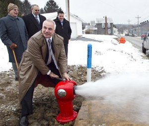 Retired firefighter and creator George Sigelakis tests the first Sigelock Spartan fire hydrant installed in Franklin, Pa. in 2010.