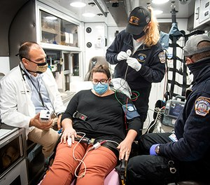 Dr. Jason Stopyra (far left) demonstrates using an i-STAT device with paramedics Callie Katers (second from right) and Bubba Killgo (far right), with Wake Forest Baptist employee Rebecca Overman standing in as a patient.