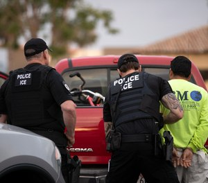 In this July 8, 2019, file photo, U.S. Immigration and Customs Enforcement (ICE) officers detain a man during an operation in Escondido, Calif. (AP Photo/Gregory Bull, File)