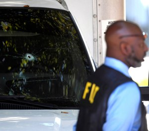 A bullet hole can be seen in the front window of a box truck where law enforcement officers where investigate after shots were fired involving Immigration and Customs Enforcement agents in the parking lot of a Food Lion store, Thursday, Sept. 5, 2019, in the Antioch neighborhood of Nashville, Tenn. (Shelley Mays/The Tennessean via AP)