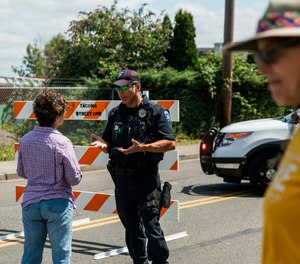 Police Officer Sam Lopez turns away would-be protesters in front of a road block near the Northwest Detention Center, Saturday July 13, 2019 in Tacoma, Wash. (Rebekah Welch/The Seattle Times via AP)