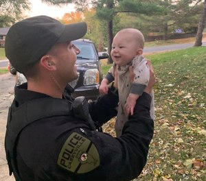 Officer Travis Hoguet holds up the infant he saved from choking on October 9, 2020.