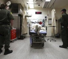 Correctional officers stand watch over an inmate receiving treatment in the emergency room at California State Prison, Corcoran. (AP Photo/Rich Pedroncelli)