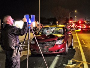 An officer uses a laser scanner to investigate the scene of an accident.