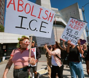 Protesters carry signs during a rally in front of the Immigration and Customs Enforcement facility in downtown Los Angeles on Monday, July 2, 2018.