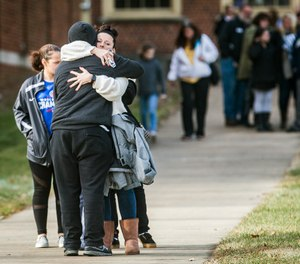 Families are reunited with their children at the Civic Hall Performing Arts Center where students waited after being bussed from Dennis Intermediate School following a shooting, Thursday, Dec. 13 2018, in Richmond, Ind.