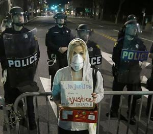 University of California Berkeley school of law graduated Alyson Reimer holds up a sign as she protests in response to police killings in Missouri and New York as Berkeley Police officers block a street in front of the police station in Berkeley, Calif., Monday, Dec. 8, 2014. (AP Image)