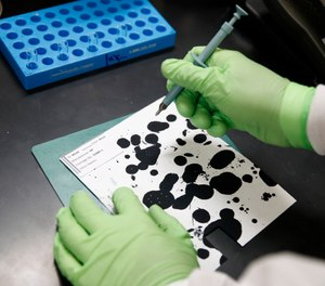 In this June 27, 2019 photo, document analysis technician Irvin Rivera collects samples of inkjet printer ink in the International Ink Library at the U.S. Secret Service headquarters building in Washington. (AP Photo/Patrick Semansky)