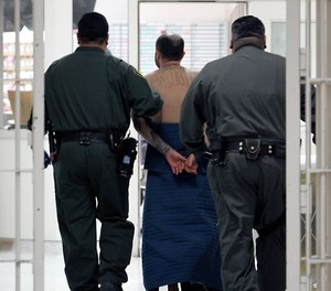 In this Jan. 14, 2009 file photo, an inmate, on suicide watch, is escorted by correctional officers at the California Substance Abuse Treatment Facility in Corcoran, Calif.