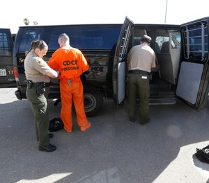 In this photo taken Thursday, Feb. 20, 2014, Shasta County Deputy Sheriff Christine Gerring, left, removes the restraints from a prisoner after transporting convicted felons from the Shasta County Jail to the Deuel Vocational Institute near Tracy, Calif.