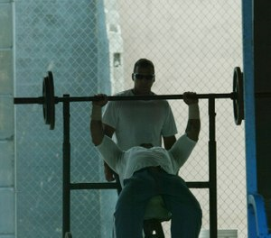 An inmate lifts weights at the Hendry Correctional Institution on Wednesday, April 11, 2007, in Immokalee, Fla. (AP Photo/Wilfredo Lee)