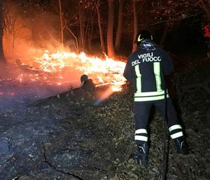 A firefighter hoses down a fire near Varese, northern Italy. (Vigili del Fuoco/Italian Firefighters via AP)