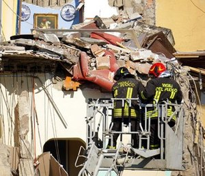 Firefighters work at the site where a building that collapsed in Torre Annunziata, near Naples, southern Italy, Friday, July 7, 2017. (Ciro Fusco/ANSA via AP)