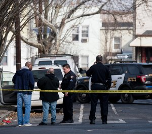 Jersey City police investigate and collect evidence on Rutgers Avenue where three Jersey City police officers were reportedly injured after a scuffle with an armed suspect.