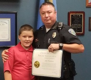 Pictured is Officer Jody Thompson and John during the Oklahoma State Bureau of Investigation ceremony that honored Thompson for his extraordinary show of humanity. (Photo/Poteau Police Department)