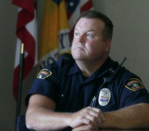 Police Officer Joe Hepler sits at the Stow station July 5. [Photo/Phil Masturzo/Akron Beacon Journal]