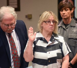 In this July 28, 2015 file photo, Joyce Mitchell raises her hand during a court appearance in Plattsburgh, N.Y.