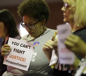 Alicia Street holds a sign as she sits in the audience during a meeting of the Ferguson City Council, Tuesday, March 15, 2016, in Ferguson, Mo.