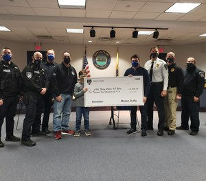 Mason Duffy and police officers pose with a check made out to the Little Ferry Police K-9 unit.
