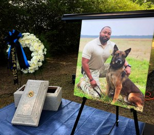 A Tuesday, July 30, 2019 photo shows Alabama K-9 Jake, who died after coming into contact with a narcotic during a prison contraband search, was honored Tuesday with a 21-gun salute and commendation from Gov. Kay Ivey at the Staton Kennel Complex in Elmore. Pictured in the portrait is Jakes handler Sgt. Quinton Jones. (AP Photo/Blake Paterson)