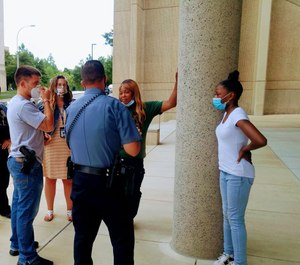 Shetara Sims and daughter Rakiya meet coworkers of the wounded officer after donating $100 they won with a lottery ticket. (Photo/ Kansas City Missouri Police Department)