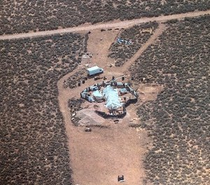 This Friday, Aug. 3, 2018, aerial photo released by Taos County Sheriff's Office shows a rural compound during an unsuccessful search for a missing 3-year-old boy in Amalia, N.M.