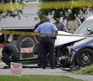 Investigators look over a New Orleans Police department vehicle in which one officer was shot and killed while transporting a prisoner in New Orleans, Saturday, June 20, 2015.