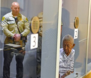 Thomas Kim sits in a hospital gown in a wheelchair as his arraignment is postponed. (Photo/AP)
