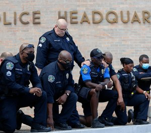 Members of the Austin Police Department kneel in front of demonstrators who gathered in Austin, Texas, Saturday, June 6, 2020, to protest the death of George Floyd. (AP Photo/Eric Gay)