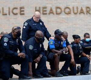 Members of the Austin Police Department kneel in front of demonstrators who gathered in Austin, Texas, Saturday, June 6, 2020, to protest the death of George Floyd.