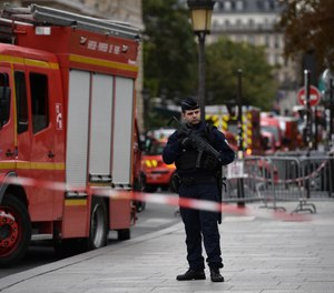A policeman stands next to firefighter vehicles near Paris police headquarters on Oct. 3, 2019 after four officers were killed in a knife attack. The attacker was shot dead after killing four officers at police headquarters in the historical centre of Paris. (Martin Bureau/AFP/Getty Images/TNS)