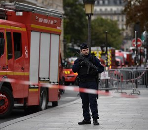 A policeman stands next to firefighter vehicles near Paris police headquarters on Oct. 3, 2019 after four officers were killed in a knife attack. The attacker was shot dead after killing four officers at police headquarters in the historical centre of Paris.