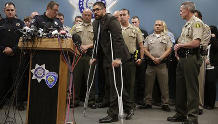 Officer Nicholas Koahou, center, walks toward the podium to answer questions during a news conference. (AP Photo/Jae C. Hong, File)