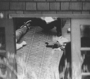 In this April 8, 1994 file photo, special investigators examine the body of Kurt Cobain, which lies on the floor of a room atop the detached garage in his home overlooking Lake Washington in Seattle. (AP Image)