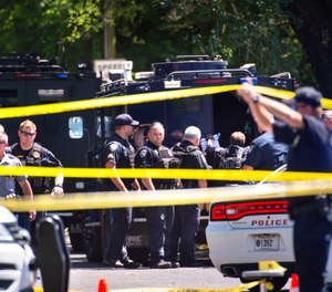 Baton Rouge Police Department officers gather at the site of a shooting in Baton Rouge, La., Sunday, April 26, 2020. (Travis Spradling/The Advocate via AP)