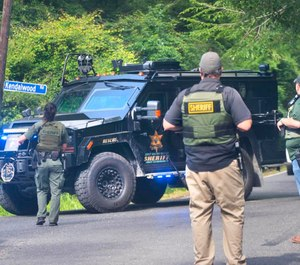 East Baton Rouge Sheriff's Office deputies stop traffic near where a search was being conducted for a suspect sought in the shooting of an EBRSO deputy.