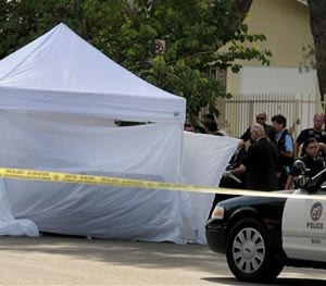 Los Angeles Police Department officers investigate the scene of a shooting Sunday, Aug. 24, 2014.