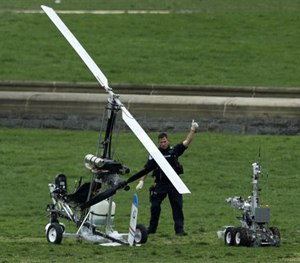 A Capitol Police officer flashes a thumbs up after inspecting the small helicopter a man landed on the West Lawn of the Capitol in Washington.