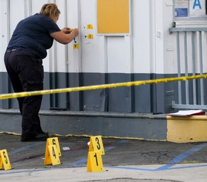 LAPD crime investigators collect evidence at one of the scenes of a shooting, a Shell gas station in the North Hollywood section of Los Angeles on Thursday, July 25, 2019. (David Crane/The Orange County Register via AP)