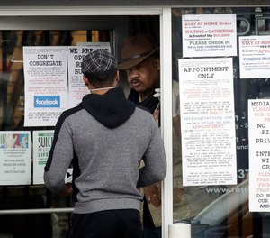 An employee answers questions at the entrance to a gun shop in Culver City, Calif. Los Angeles County Sheriff Alex Villanueva said he would like to see gun shops shut down.